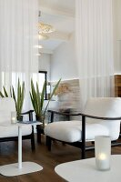 White cushions on black armchair frames and purist side table in front of delicate curtain used as partition