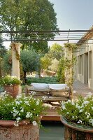 Mediterranean wooden deck with potted plants and rustic tree-trunk sofa