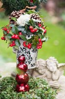 Christmas arrangement in antique vase and stone angel figurines