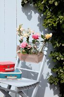 Bottles of flowers in window box and small, colourful, retro suitcases on garden chair against white wooden wall