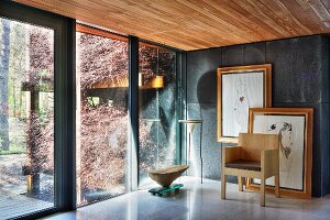 Drawings and objets d'art in interior with glass wall leading to garden and view of bundles of brushwood on wooden rack