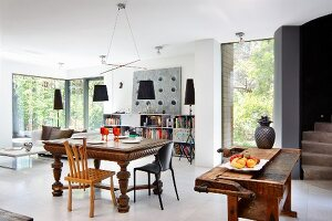 Dining area with antique table and workbench used as rustic kitchen counter in open-plan interior