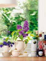 Oil bottles and nostalgic coffee set decorated with flowers on windowsill