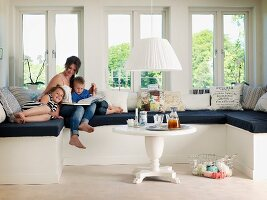 Mother and children on window seat with black seat cushion in renovated, white, country-house interior