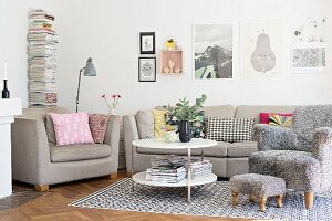 Ecru sofa set and comfortable armchair with grey fluffy cover and matching footstool on rug in living room