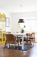 Retro chairs at white dining table below pendant lamp next to display case with yellow frame