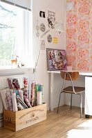 Rolls of wrapping paper in wooden crate below window, clip-on, retro desk lamp and retro, wooden chair at white table