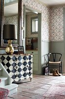 Chequered chest of drawers in rustic foyer with Tessin wallpaper design and classic chair in corner
