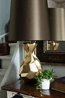 Table lamp with sculptural brass base and dark brown lampshade