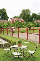 Garden table and chairs on lawn in front of horse in paddock of country estate
