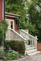 External steps with stone treads and wooden balustrade leading to Falu-red country house