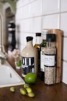 Olives and limes next to spice jars on worksurface