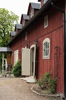 Country house with small flowerbeds against wooden façade painted Falu red