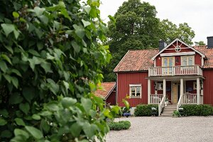 View from garden to Falu-red country house with white-painted balcony over porch with steps
