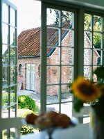View of garden and small brick house through open French doors