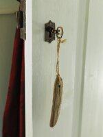 Key with wooden key fob in lock of wooden door