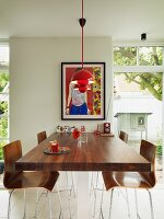 High, walnut table abutting wall and bar stools with wooden shell seats below red pendant lamps and between French windows