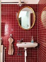 Sink below oval gilt-framed mirror on red-tiled wall in corner of modern bathroom