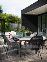 Grey cane chairs around rustic wooden table on terrace with wooden deck