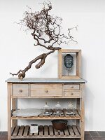 Gnarled branch and head of Buddha in wooden frame on top of simple wooden sideboard with drawers and shelves