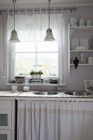 Sink unit with two round basins and curtain below window in shabby-chic kitchen