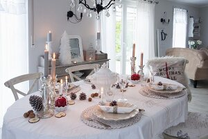 Lit candles on dining table festively set for Christmas in shabby-chic interior