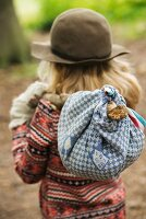 Blonde girl carrying picnic in bindle in autumnal garden