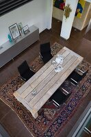 Eclectic furnishings in open-plan interior seen from above; rustic table and black designer chairs