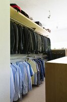 Suit jackets and shirts hanging from clothes rails in walk-in wardrobe