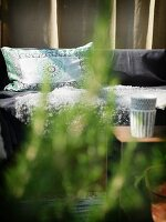 Patterned cushions on bench seen through green leaves