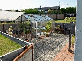 Rückzugsort in bewohnbarem Gewächshaus auf gekiester Fläche im Garten