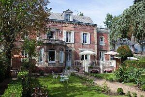 Sunny garden of traditional 19th-century, brick villa