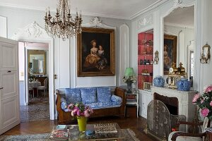 Elegant interior with stucco elements on wall, Biedermeier couch and fireplace