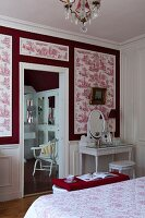 Dressing table against red and white toile de jouy wallpaper in bedroom