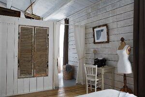 Fitted wardrobe with wooden louvre doors in partition, small desk against wall and vintage tailors' dummy in rustic bedroom