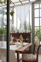 Antique furniture and floral crockery on dining table in vintage-style conservatory