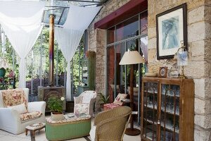 Antique furniture, wicker chairs in seating area and crystal glasses in olf display cabinet in vintage-style conservatory