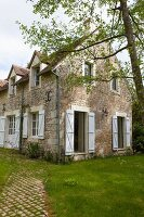 Rustic stone country house with white shutters and window in summer garden
