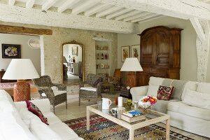 Pale sofa set and coffee table in living room in renovated country house with whitewashed wood-beamed ceiling