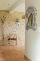 Mirror with carved frame, Scandinavian-style armchair and vintage pitchfork hung on stone wall