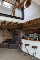 Retro bar stools at counter and seating area under gallery in rustic country house