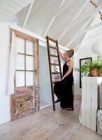 Schwarz gekleidete Frau an rustikaler Holzleiter in ländlichem Sommerhaus mit weiss gestrichener Holzverschalung im Innenraum