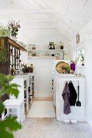 Kleine, funktionale Küche in weiss gestrichenem Holzhaus