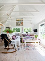 Schaukelstuhl neben gemütlichem Ecksofa mit vielen Kissen in kleinem Sommerhaus mit weisser Holzverschalung im Innenraum