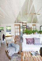 Schaukelstuhl mit Tierfell neben teilweise sichtbarer Bank, in offenem Wohnraum mit weiss gestrichener Holzverschalung
