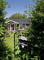 Blick von sommerlichem Garten auf kleines Sommerhaus mit weissen Sprossenfenstern