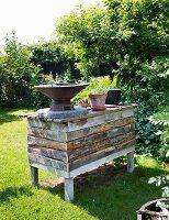 Aus Holzbrettern gezimmerte Theke mit Aussengrill und Blumentöpfen, in sonnigem Garten