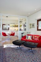 Glass sliding doors between dining area and living area; red designer couch and black leather footstools