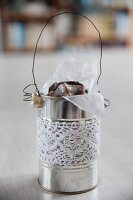 Tin can decorated with lace trim and used as biscuit tin