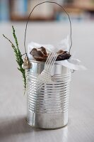 Tin can decorated with ribbon, beads and conifer sprig and used as biscuit tin